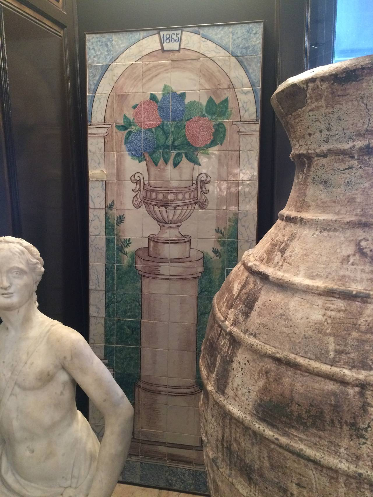 A 19th century polychrome mural representing a flower vase over a column in a marbled niche, dated 1865. The manganese urn holds blue and red hydrangeas.