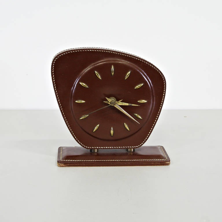 Table clock designed by Jacques Adnet. Manufactured in France around 1950. All in leather with brass details.  In good original condition, with minor wear consistent with age and use, preserving a beautiful patina.