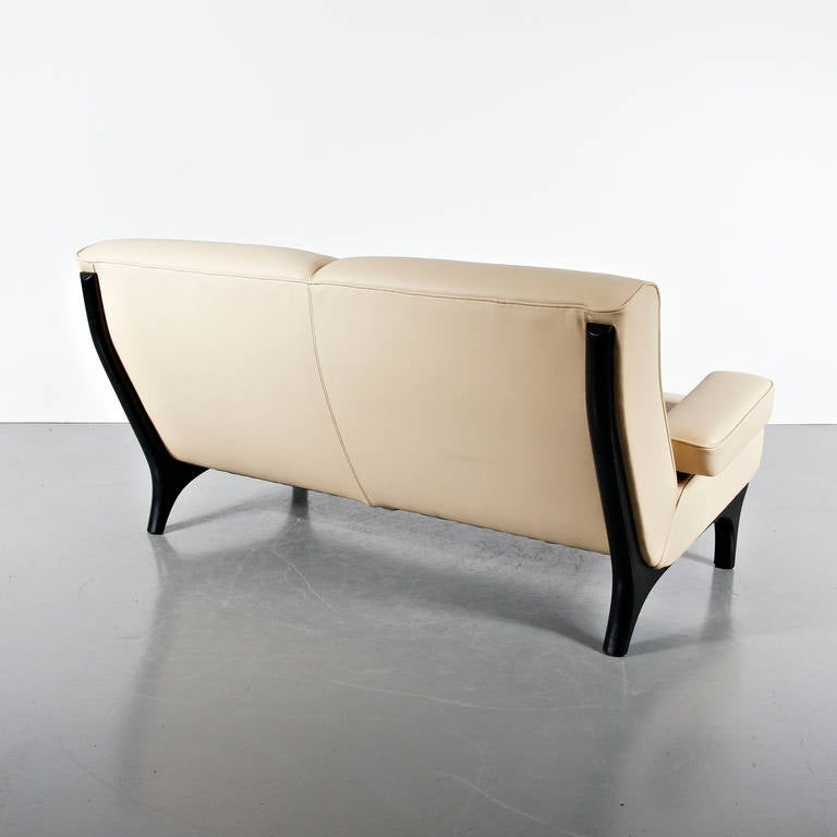 Stunning cream white two-seat sofa designed by Eugenio Gerli, manufactured by Tecno in Italy, circa 1960.  This eye-catching sofa has a black lacquered wooden base. It is upholstered in the most beautiful cream white leather. This color scheme