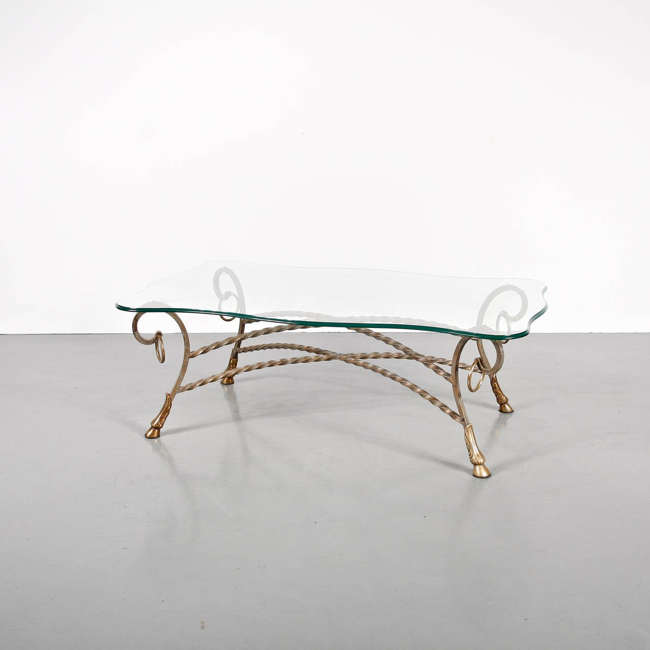 Glass coffee table in the manner of Maison Jansen manufactured in France, circa 1960. High quality glass and brass sculptural structure.  In good original condition, with minor wear consistent with age and use, preserving a beautiful patina.