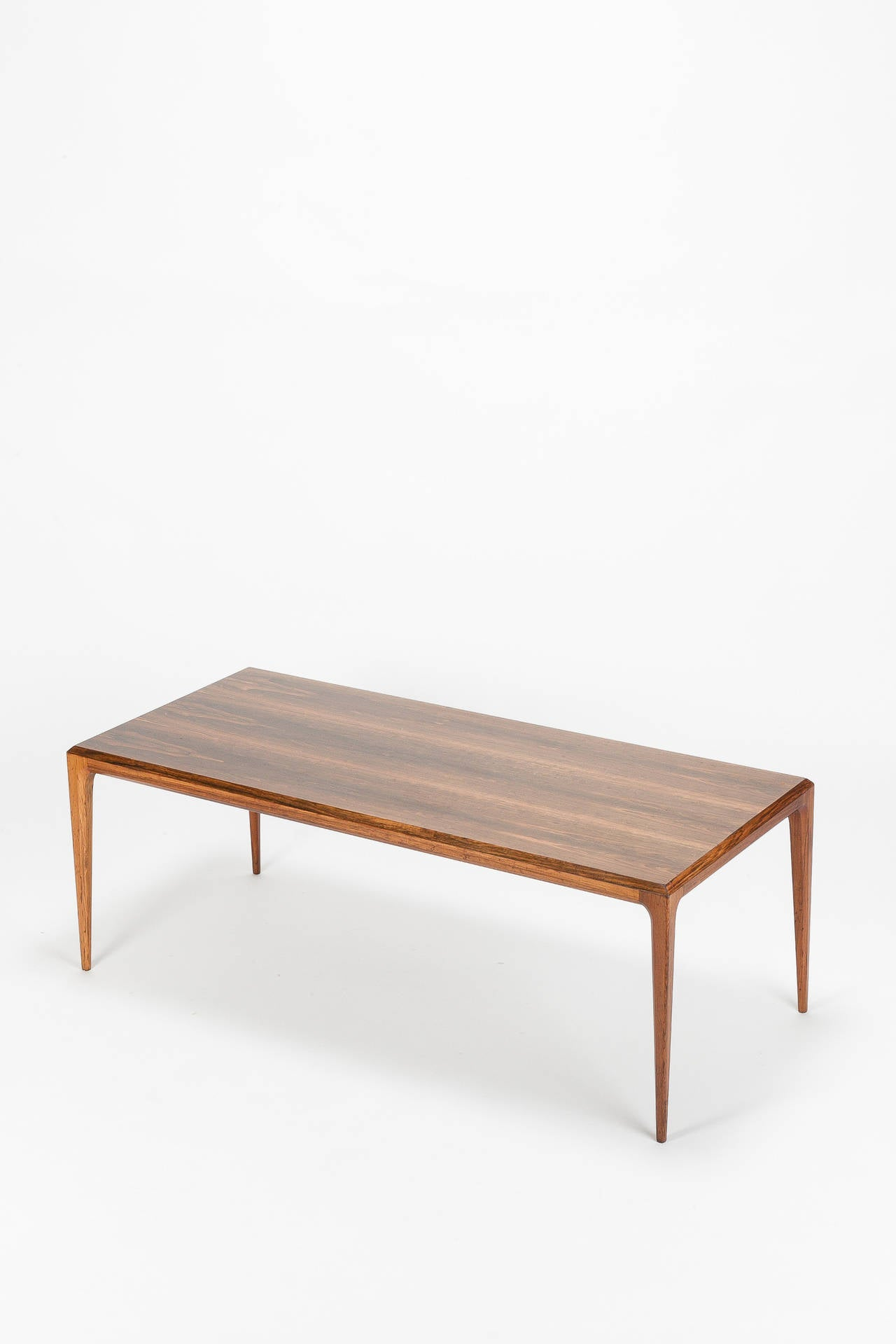 Danish coffee table designed by Johannes Andersen for CFC Silkeborg in Denmark, 1960s. Made of beautiful grained rosewood, very unique and elegant shape with canted edges and conical shaped legs.