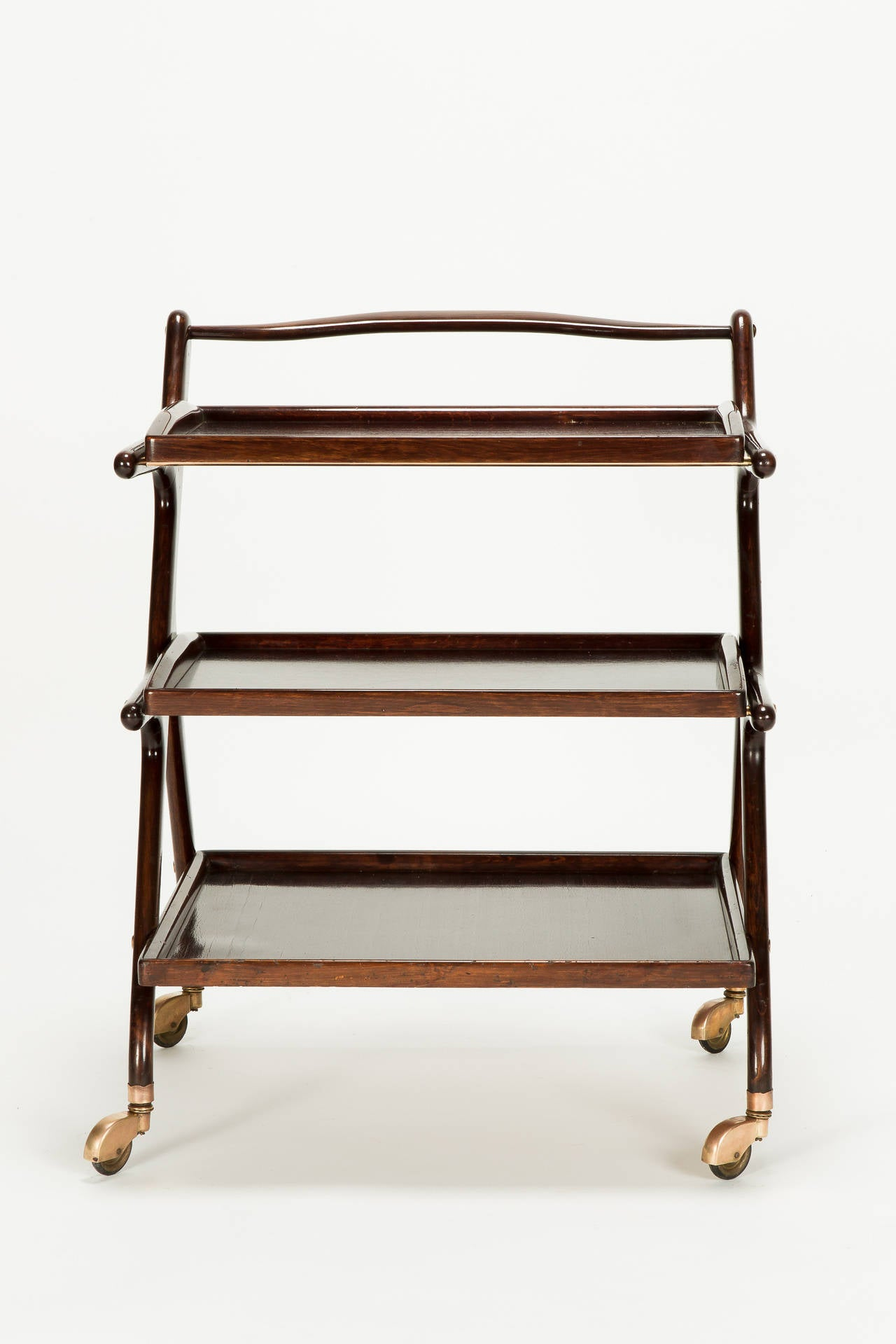 Italian mahogany serving trolley by Cesare Lacca, Italy, 1950s. Two removable trays, on brass wheels (slightly bronze colored), original finish.