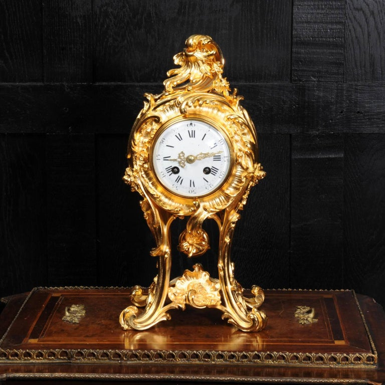 A stunning antique French clock, finely modelled in ormolu (finely gilded bronze). It is a beautiful Rococo balloon shape, flamboyant acanthus legs hold the movement aloft and the original ormolu pendulum is visible, swinging gently below. Above the