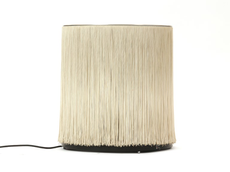 A pair of table lamps of cylindrical form with six sockets obscured by a curtain of silk strands and a single uplight.