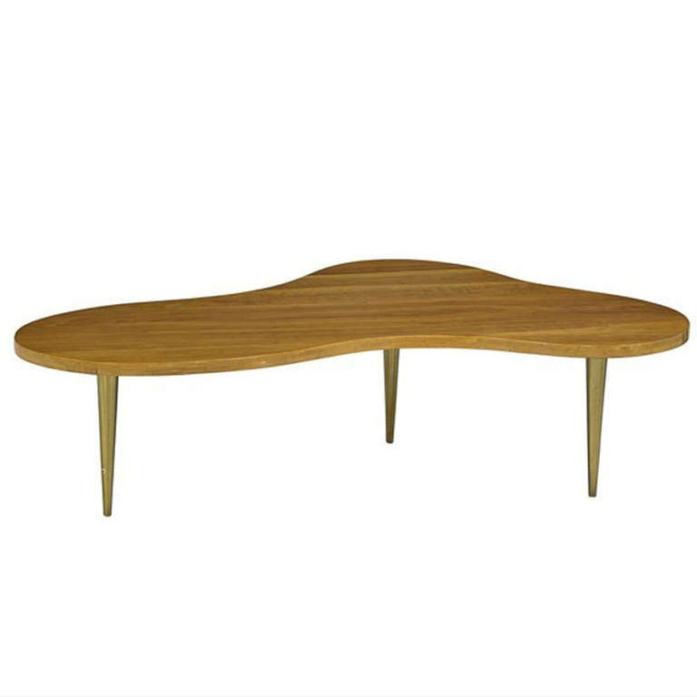 The organically shaped coffee table is in birch and brass and was made for Widdicomb, with a manufacturer's label is underneath.