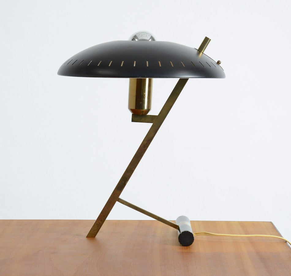 This beautiful desk lamp was designed by Louis Christiaan Kalff for Philips, Eindhoven in 1955. It has a black curved perforated shade and a brass frame. It is in good vintage condition.