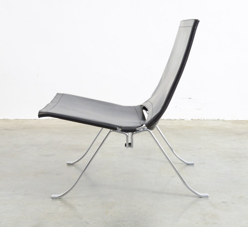 This easy chair is designed by Preben Fabricius for Arnold Exclusiv in 1971. The frame is made of thick nickeled steel. The thick black saddle leather back and seat are tied together at the back. This high quality timeless minimal chair is rare to