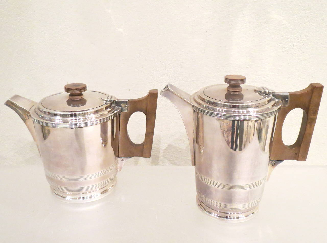 Four-piece silver plate tea and coffee service, stepped Art Deco bases and lids, with wood handles, comprising a coffee pot, tea pot, sugar and creamer by Walker and Hall Sheffield. Measurements: Coffeepot height cm 17.5, width cm19, depth cm 10.5.