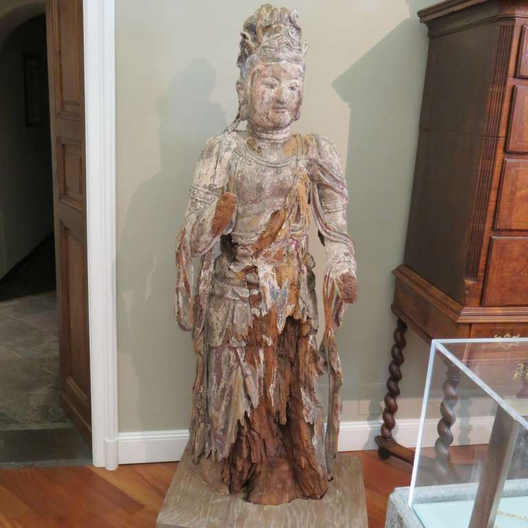 Early Ming standing carved wood Bodhisattva Avalokiteśvara (Guanyin), China 1368-1644. This massive Bodhisattva Guanyin is depicted here in the form of a very detailed, painted-wood statue. The paint has faded with time, leaving behind the