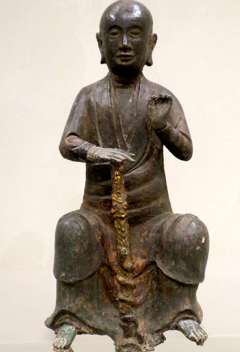 Cast seated wearing a simple robe with his right hand resting on the hilt of a snake-entwined sword, the left hand held aloft, his face with meditative expression.