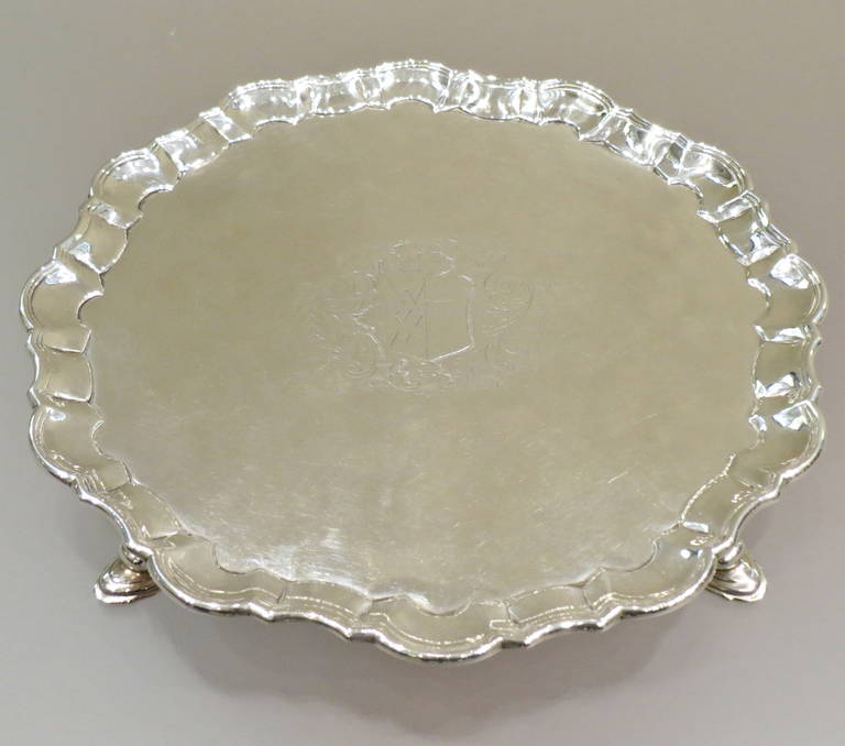 A George II silver salver with wavy outline, set on three stepped pad feet, with an imposing coat of arms, London, 1735.  Dimensions: Height 3 cm; diameter 27.5. Weight 764 grams.