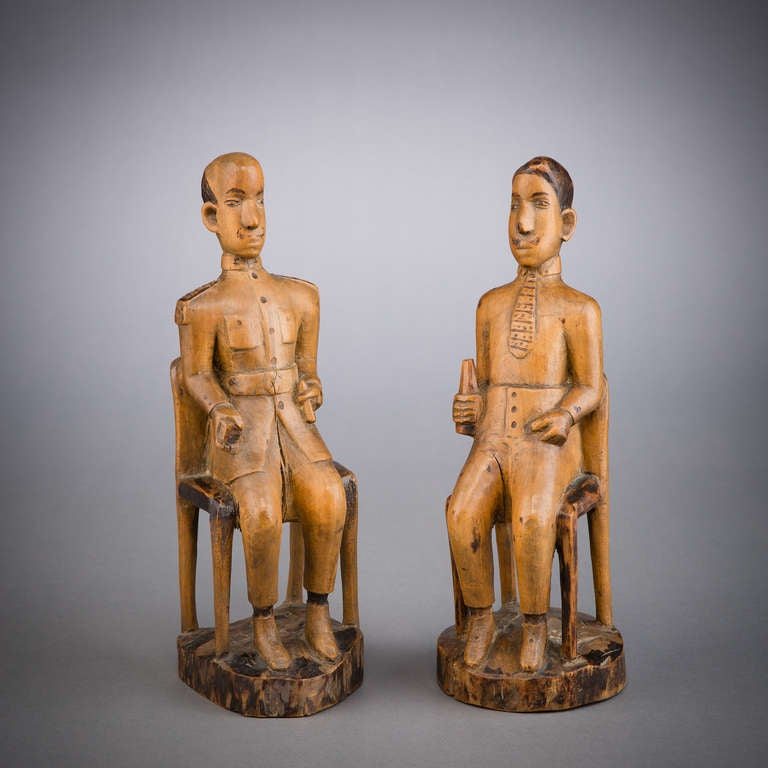 This pair of seated male figures, carved of light-hued wood and treated with pokerwork details, depicts two colonial administrators.  With the advent of colonization,  African carvers began to work European subjects into their repertoires, and in