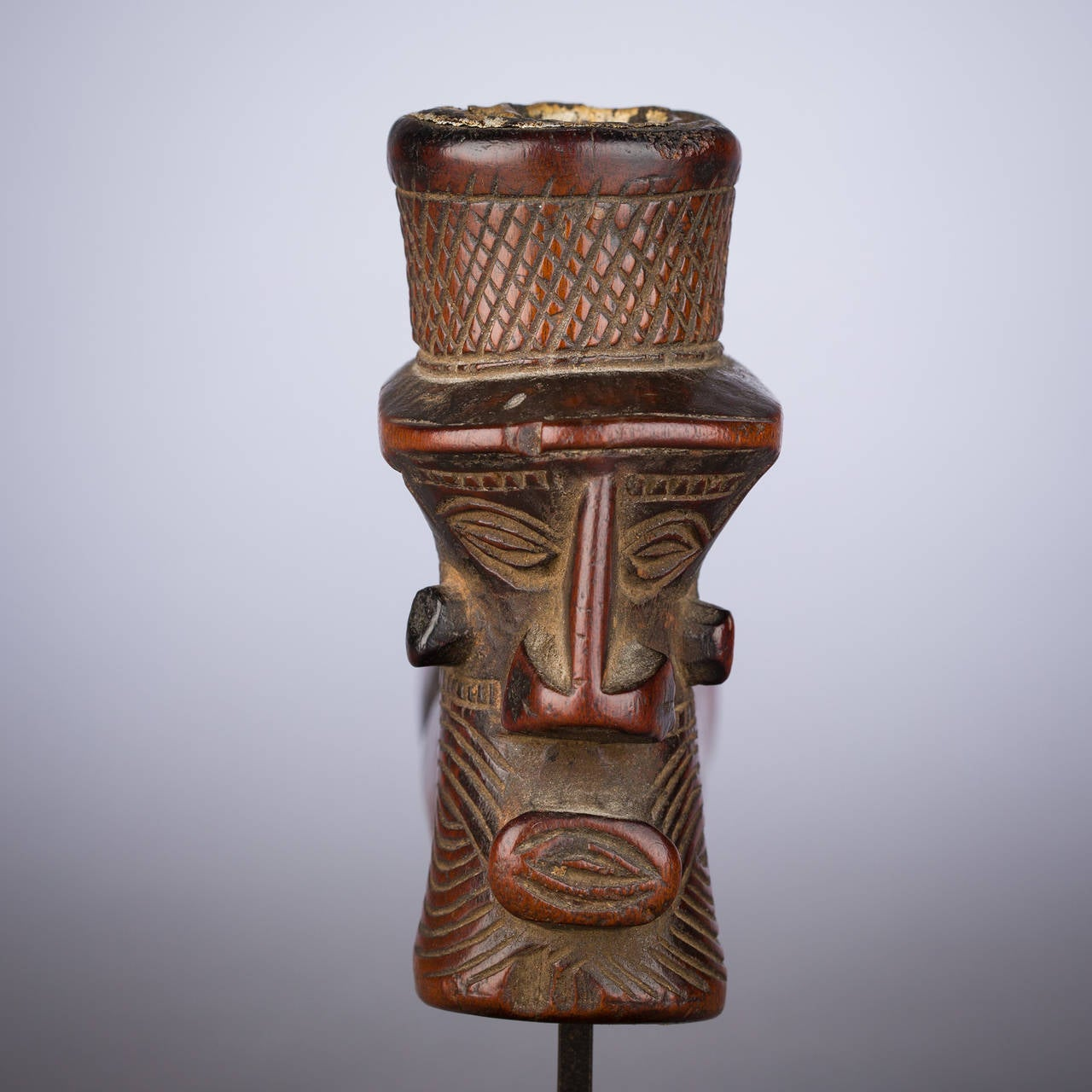 A beautiful interplay of raised planes and clustered incisions structures this impressive cephalomorphic Congolese pipe. Flowing line work textures the head, which joins with the bridge of the robust nose to present a strong, hatchet-like profile.