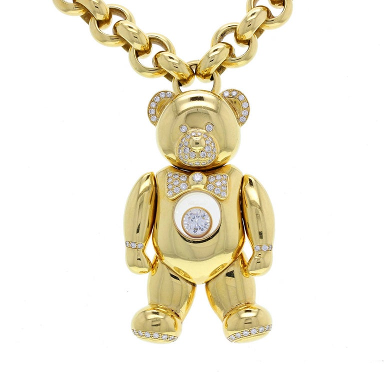 A charming teddy bear formed in 18 carat yellow gold with pave diamond detailing. Moveable arms, legs and head. Beneath the diamond-set bow tie is the famous Chopard 'Happy Diamond' - floating between to pieces of sapphire crystal, signed 'Chopard'.