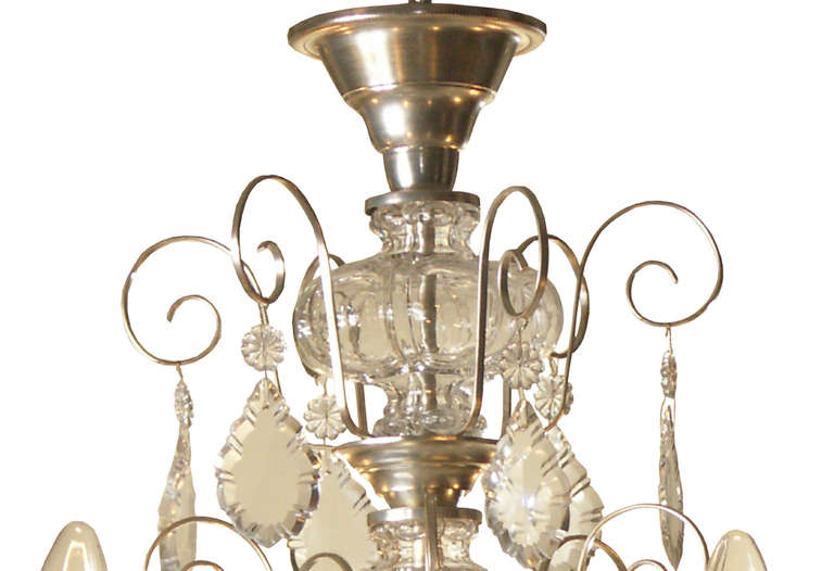 A typical Austrian post-war manufactured chandelier, delicate works with hand-cut crystal hangings, a handblown column and six flames.