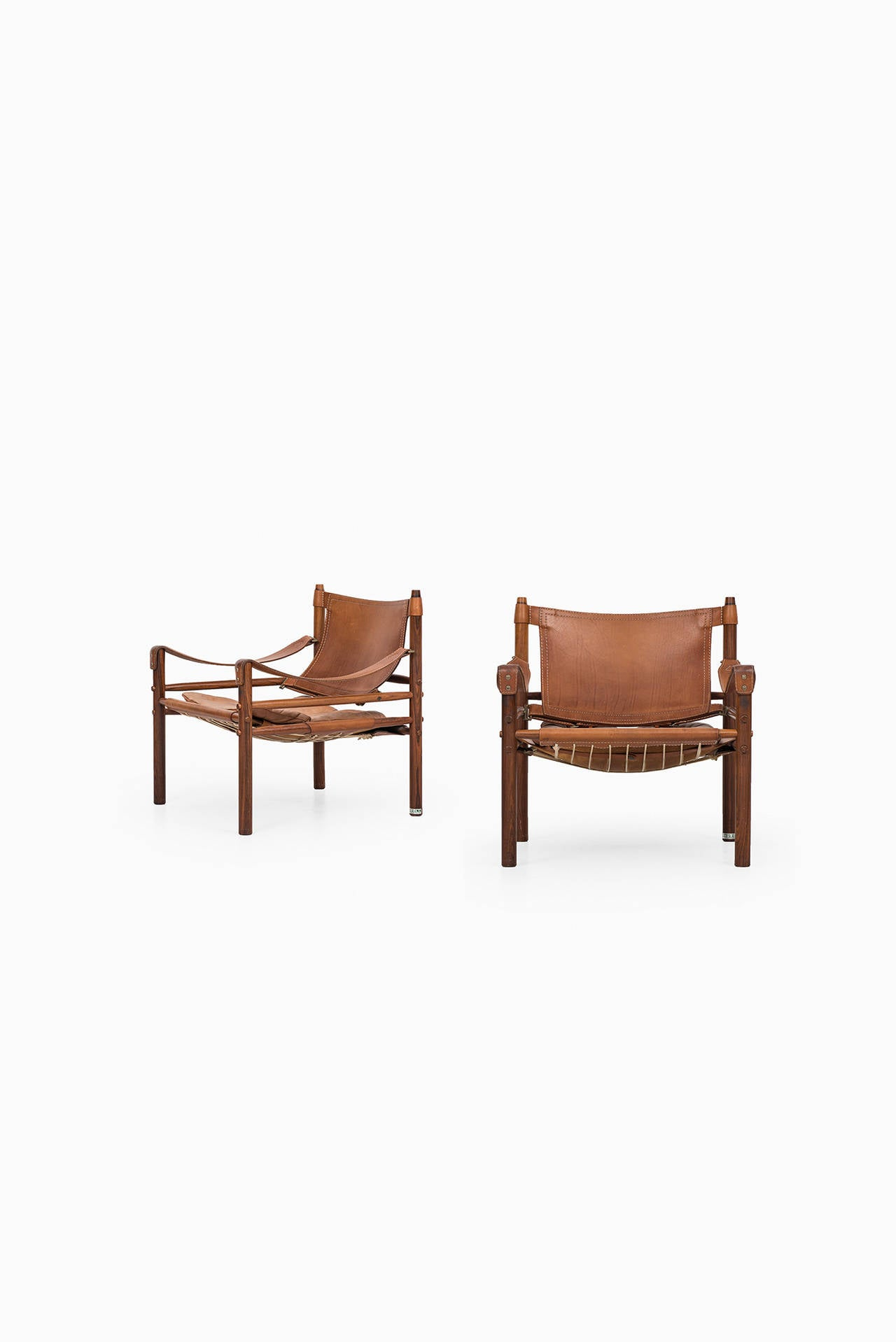 A pair of safari chairs model Sirocco in rosewood and brown leather designed by Arne Norell. Produced by Arne Norell AB in Aneby, Sweden.