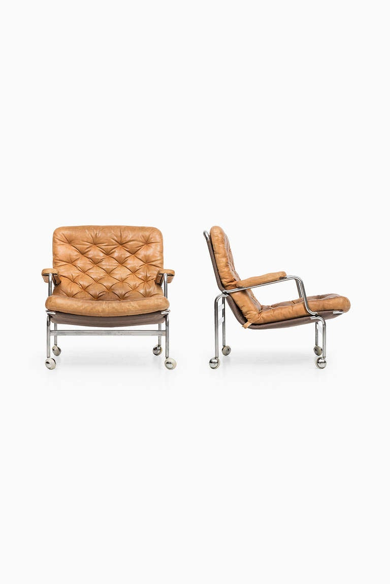Bruno Mathsson easy chairs model Karin in steel and cognac brown leather. Produced by DUX in Sweden.