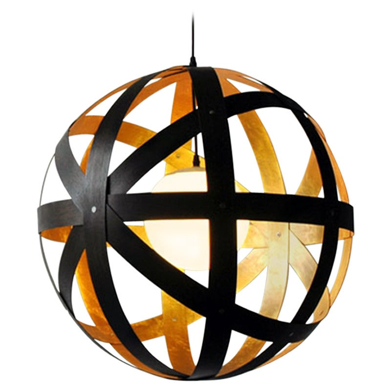 """The Meridian 24"""" pendant is a study in implied motion. Bands of locally sourced black and gold leaf walnut surround a glass orb mounted and hung from a cord and aluminum canopy.  Meridian is a versatile product and can be specified in five"""