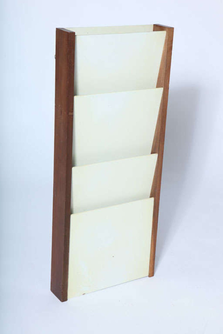 Wall mount magazine holder by Peter Pepper Products. Signed with metal label, USA, circa 1970.  Features a walnut wood frame with white laminate dividers. Some vintage wear.  Measures: 33 inches high x 14 inches wide x 3.5 inches D.