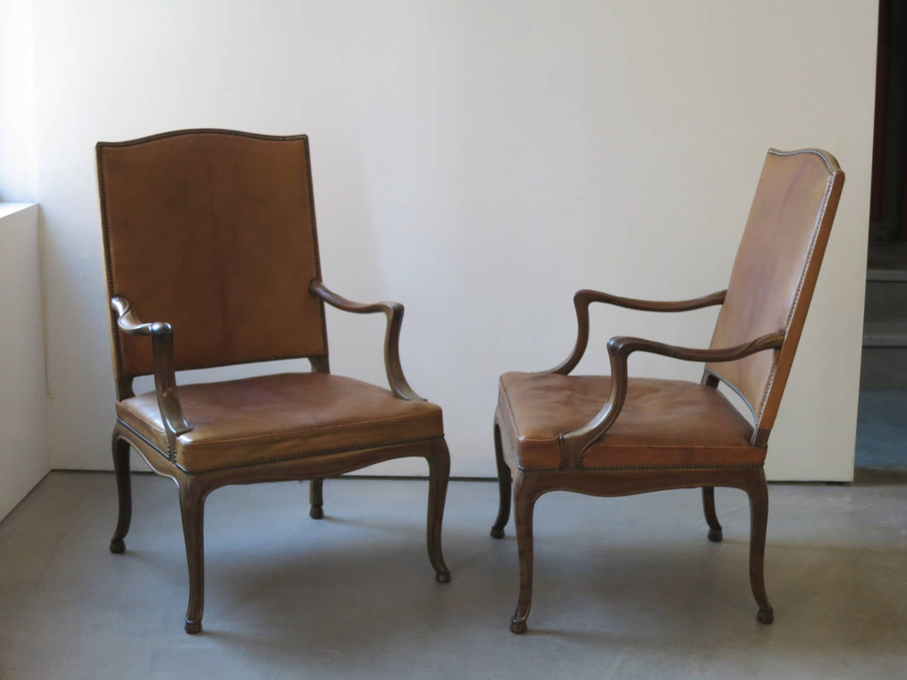 Frits Henningsen Four Large 1930s Armchairs in Danish Rococo Style. This unusual set of four large armchairs represents Frits Henningsen's modernist pared-down interpretation of Rococo style. The carving of the Cuban mahogany frames is of an