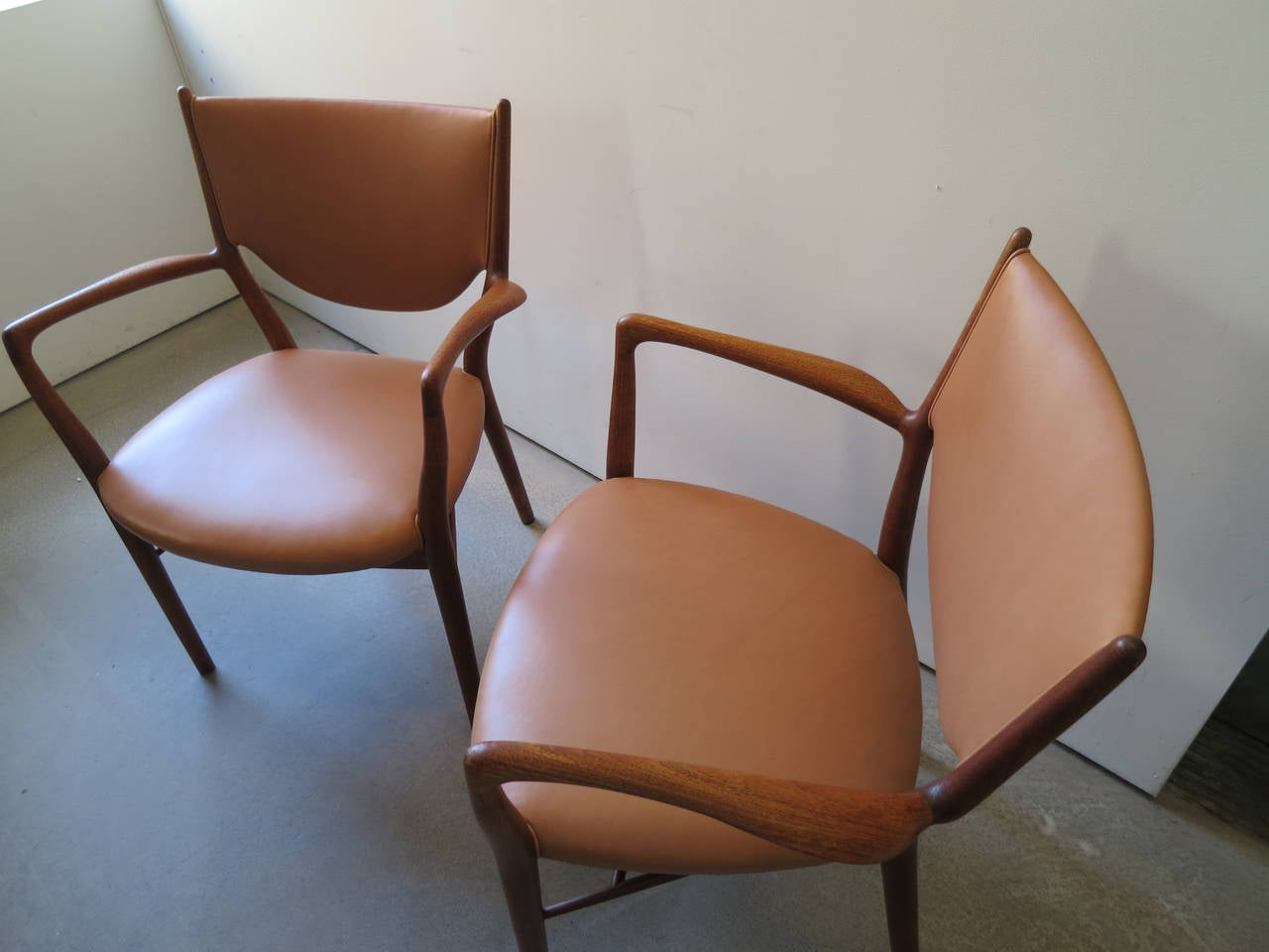Pair of NV46 Chairs by Finn Juhl in Teak with Natural Leather Upholstery.