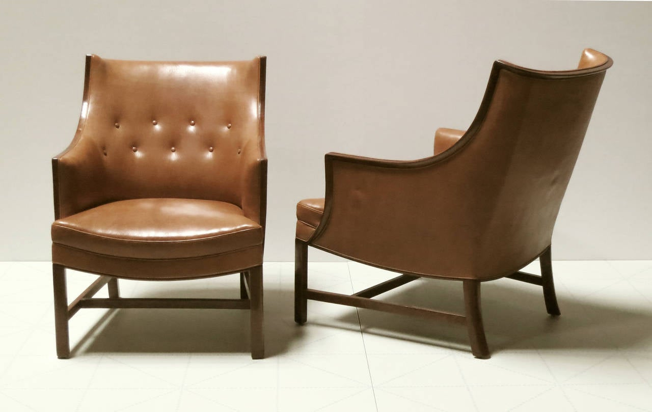 Offered by Vance Trimble, Pair of Refined 1930s Easy Chairs by Frits Henningsen.   These well proportioned and very comfortable lounge chairs feature a finely detailed trim of Cuban mahogany that sweeps around the back and down the arms creating a