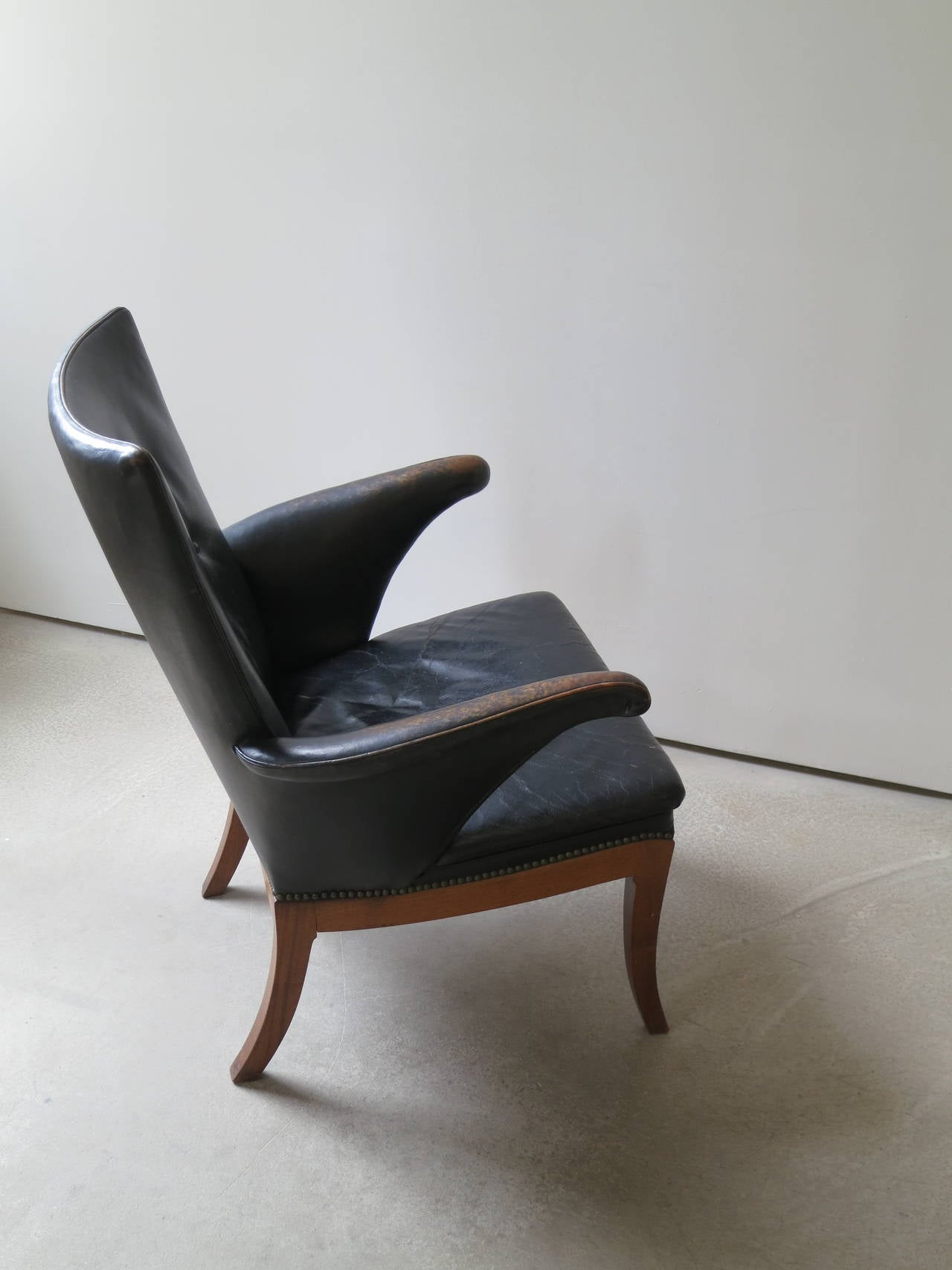 Armchair in Original Black-Brown Leather by Frits Henningsen, 1930s. This chair, which dates to the 1930s, retains its original patinated black-brown leather upholstery and brass nailheads.