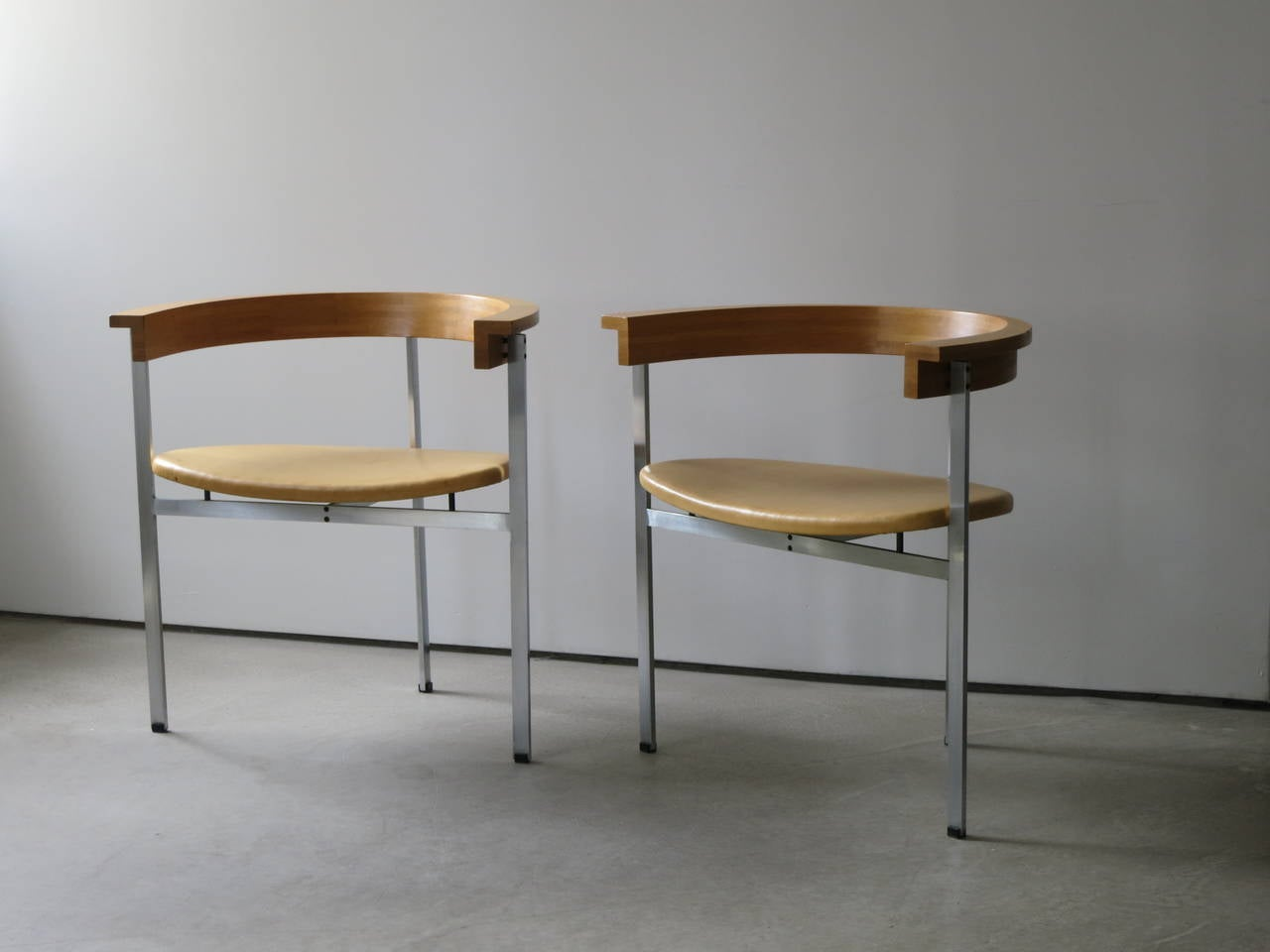 Pair of PK-11 Armchairs by Poul Kjærholm, made by E. Kold Christensen. Kjærholm designed a total of seven three-legged chairs over the course of his career. This is his most famous. This iconic chair, designed in 1957, is acclaimed for the superb