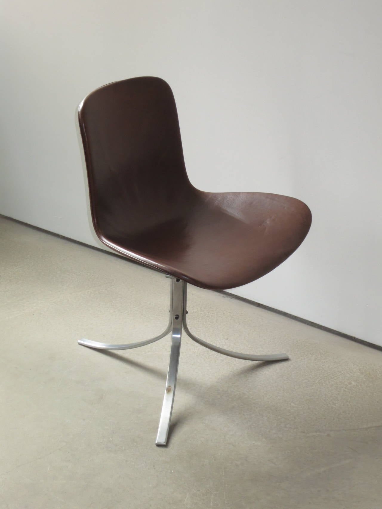 PK-9 Chair by Poul Kjærholm in patinated brown leather. Designed in 1960 and considered one of Kjærholm's masterpieces as well as a masterpiece among all 20th century chairs, the leather seat and back of this chair floats on three beautifully curved