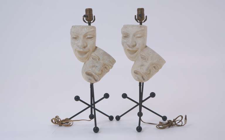 Pair of matching Frederic Weinberg Comedy and Tragedy Table Lamps.  Heavy plaster masks and solid steel frame with original wood balls.  No shades.