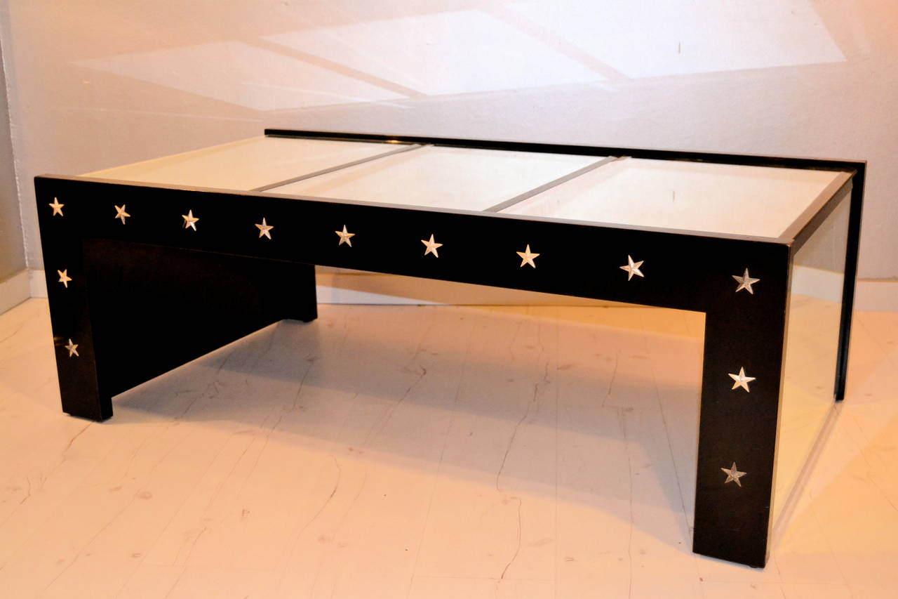 1970s mirrored coffee table and black lacquered. The table is decorated with metal stars.