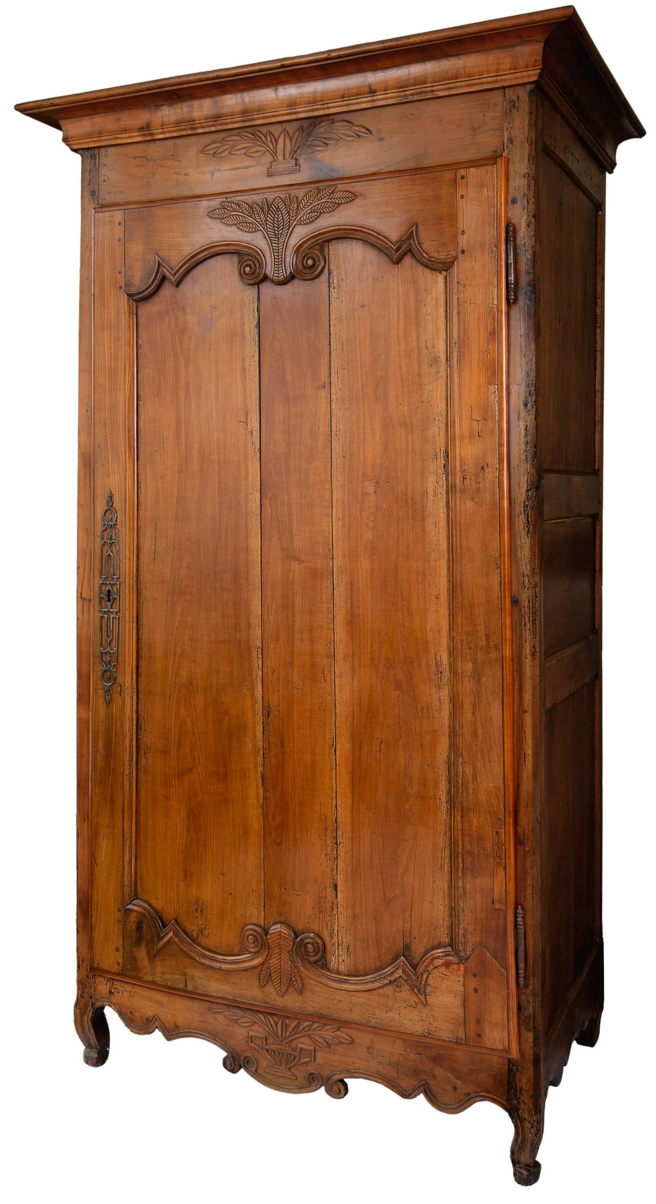 Louis XV walnut bonnetiere with original lock and decorative face plate, hinges and key. This handsome one door cabinet has a recessed panel with scrolls, wheat and cricket detail. The top and bottom apron have wheat and basket details. The shaped