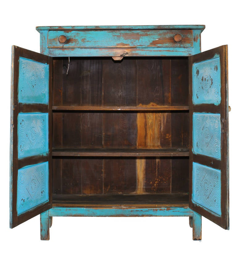 The color of the original paint on the cabinet and the punched tin makes this piece a standout in any room. The hardware is original.