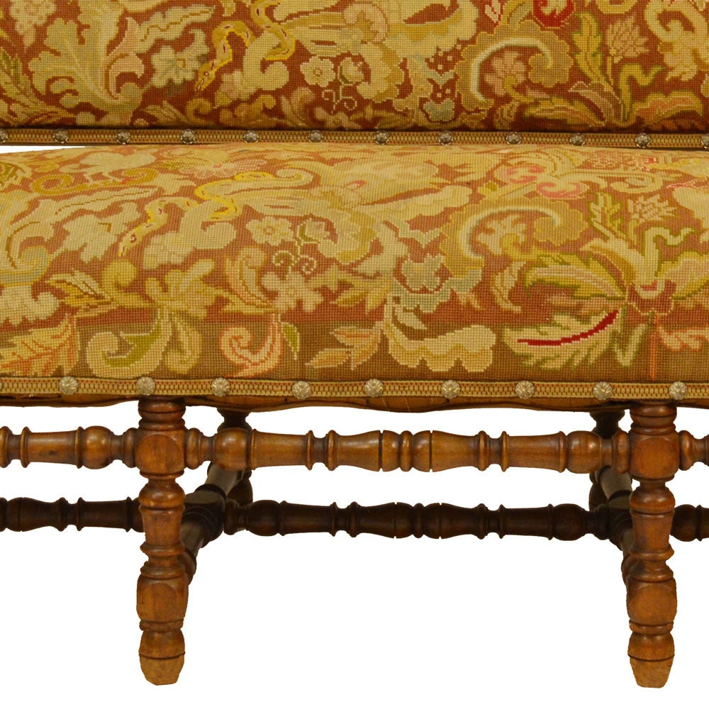 English Lancashire County Country settle upholstered in the original needlepoint tapestry with a beautiful design motif in greens, golds and browns. This settle is very sturdy, constructed in solid walnut. Measures: Seat depth: 25