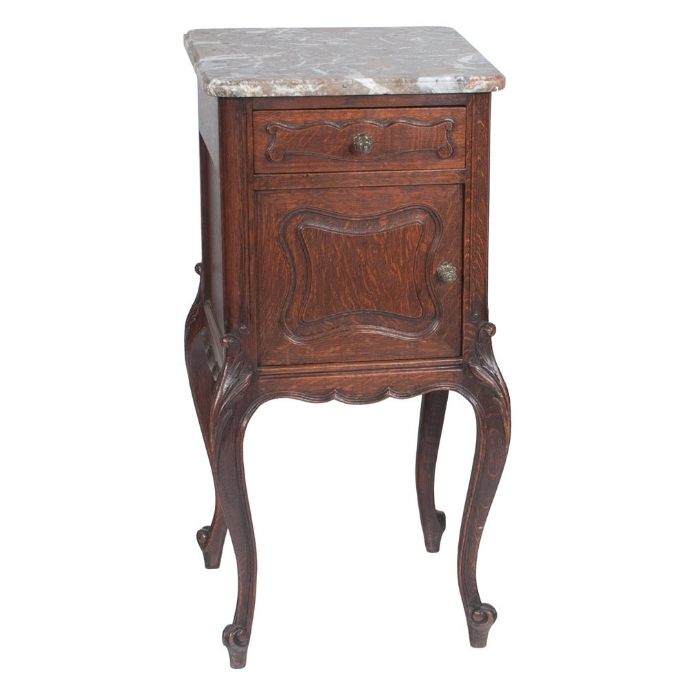 Pair of country French oak marble-top stands with one drawer over a panel door, circa 1900.