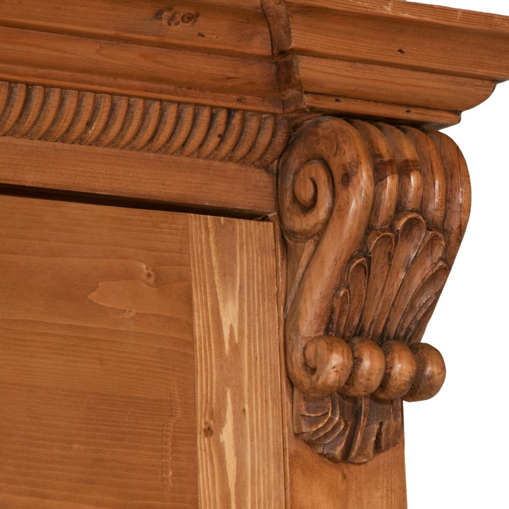 Country pine linen press. Upper section has arched panel pocket doors. Base has two drawers over double panel doors. Crown molding is supported by hand-carved corbels. Inside the doors is a feature of Classic motif hand carving...a top open panel.