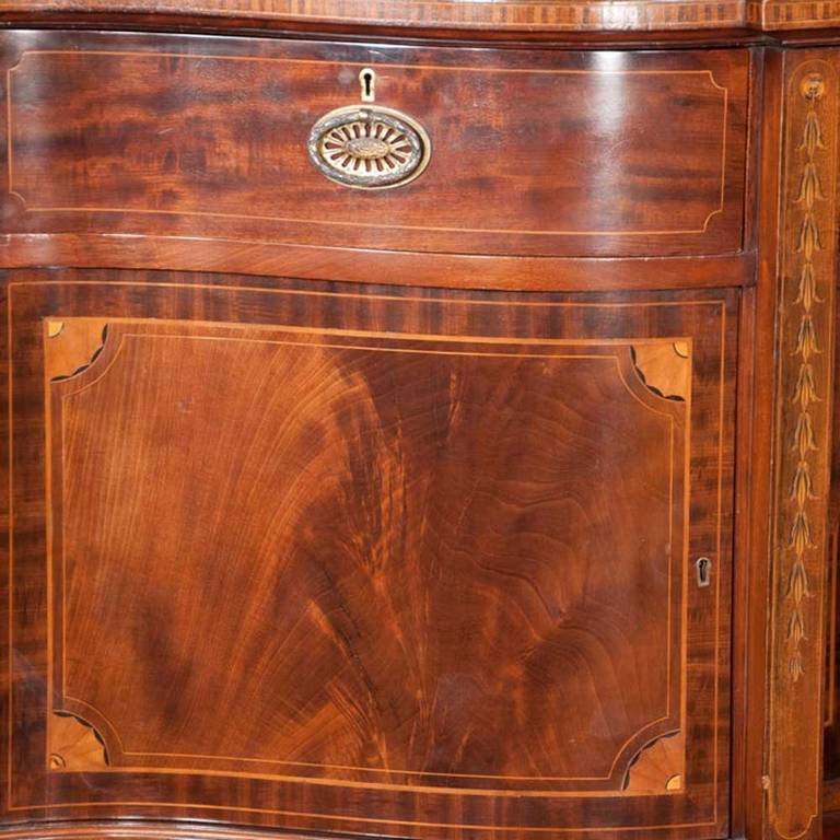 19th century English Sheraton solid mahogany sideboard with bowed front, satinwood quarter fan and bell flower inlay, brass gallery and tapered legs. It features three drawers and four doors with ample storage for silver, China and linens.