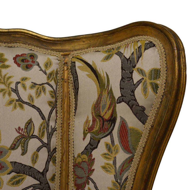 Pair of exceptional Louis XV bergères upholstered in a French brocade fabric, featuring a bird and floral scene. Gold gilded finish with hand-carved detailing and new upholstery. In pristine condition, circa 1895.