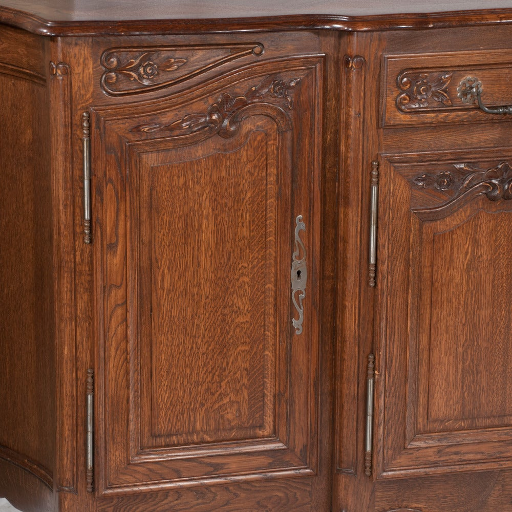 Country French oak shaped front buffet with carved panel doors on each end, center section has two drawers over two carved panel doors and having shaped carved apron, c. 1900...in very good condition with no deep scratches or cracks.