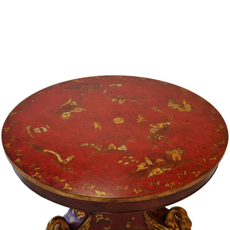 Exception Regency-style crimson and gold chinoiserie lacquered library or foyer table. It features three gilded hand-carved swans at the base of the pedestal; in pristine condition.