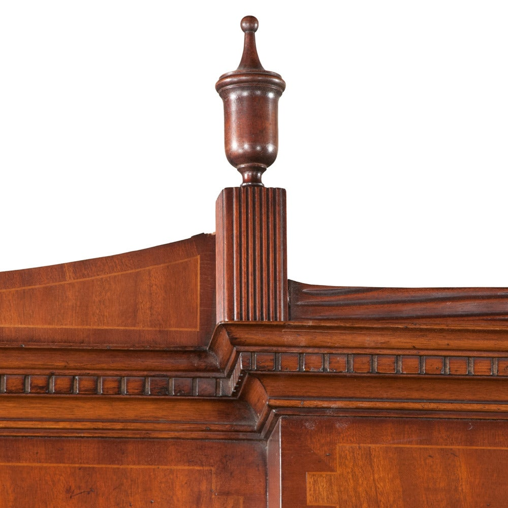 Sheraton style mahogany breakfront bookcase with shaped pediment, urn carved crest, mullion glass doors and four doors in the base with satinwood urn and oval inlay in the doors. Breakfront has ample storage behind four doors with shelving.