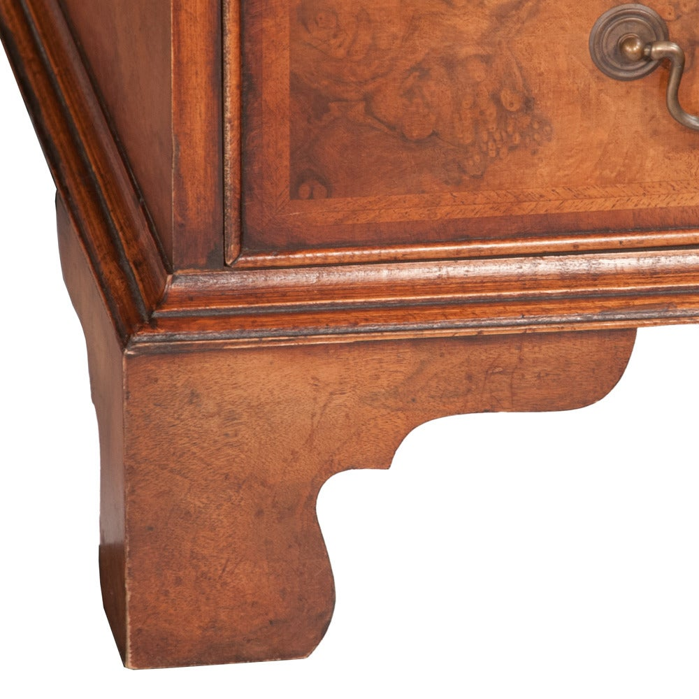 Chippendale style walnut pedestal desk with inset gold tooled leather top. Drawers are banded with herringbone inlay and it sits on bracket feet. Desk features all original antique brass pulls. Has ample storage ready for any office.