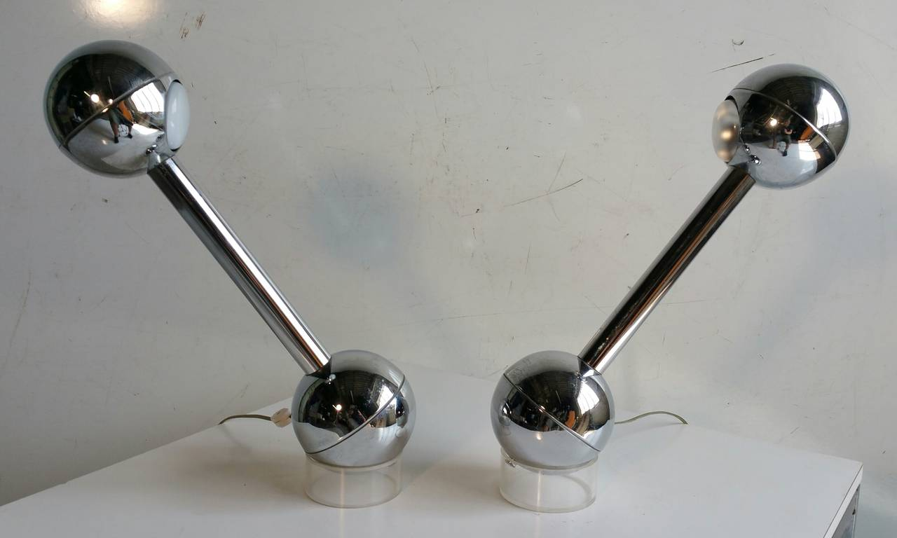 Great pair of Barbell lamps designed by John Mascheroni. The metal lamp bodies sit on acrylic cylinderical bases and are turned on / off by moving the lamp forward and back on their bases.