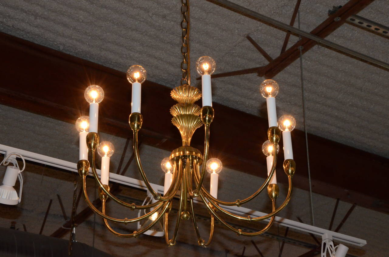 Offered is a Mid-Century Modern Tommi Parzinger style brass decorative chandelier with ten sculptural arms. The attention to elegant, yet clean and Classic design makes this chandelier so desirable some fifty years after its production. Would go