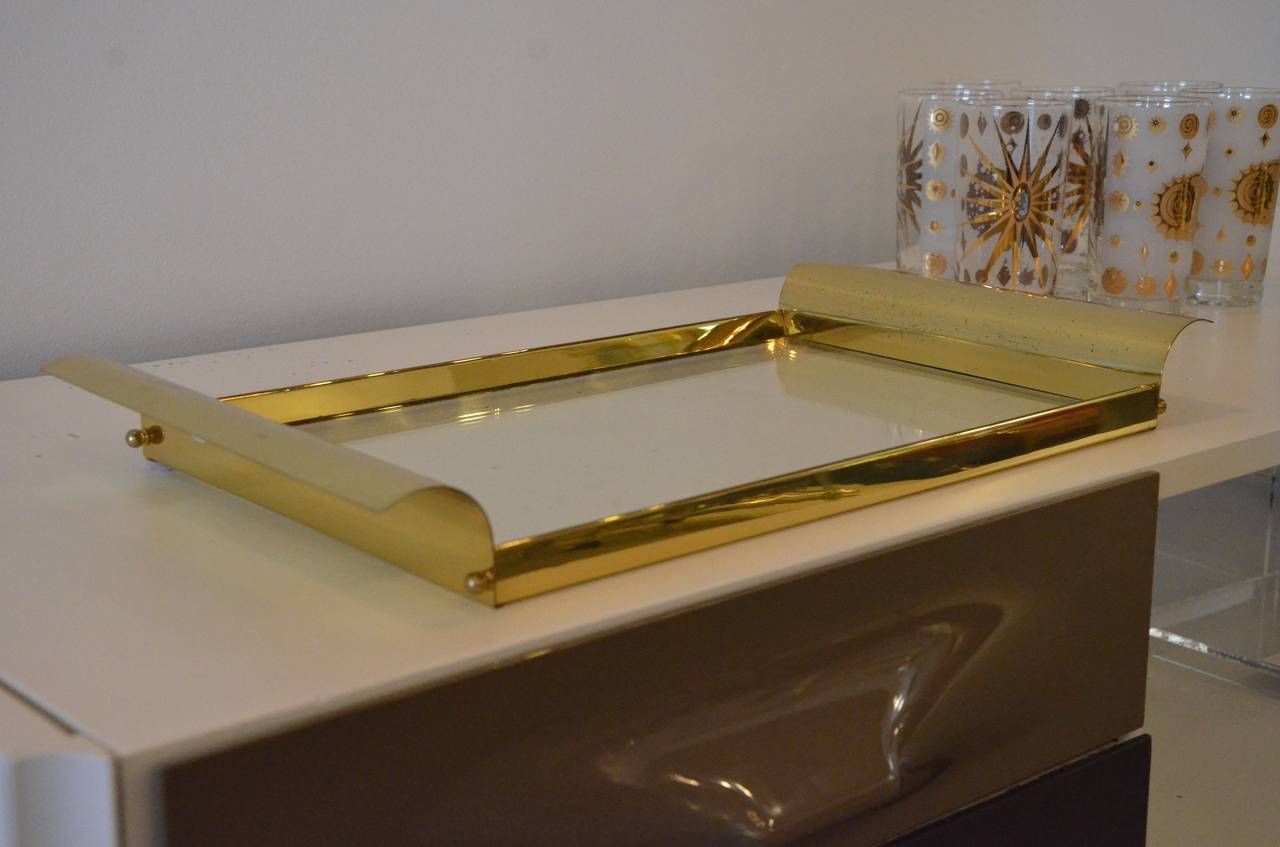 Offered is a brass and glass tray in the manner of Tommi Parzinger.  This versatile shiny brass and glass tray would look fabulous with vintage cocktail ware or with a beautiful vintage perfume bottle collection.  The design is classic and clean,
