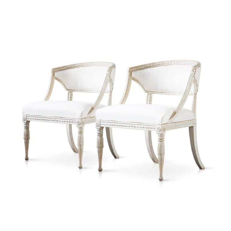 A stunning pair of Swedish Gustavian barrel back armchairs. Curved back rail, richly carved front legs and backward-curving back legs. Attributed to Ephraim Stahl, Stockholm, circa 1810.