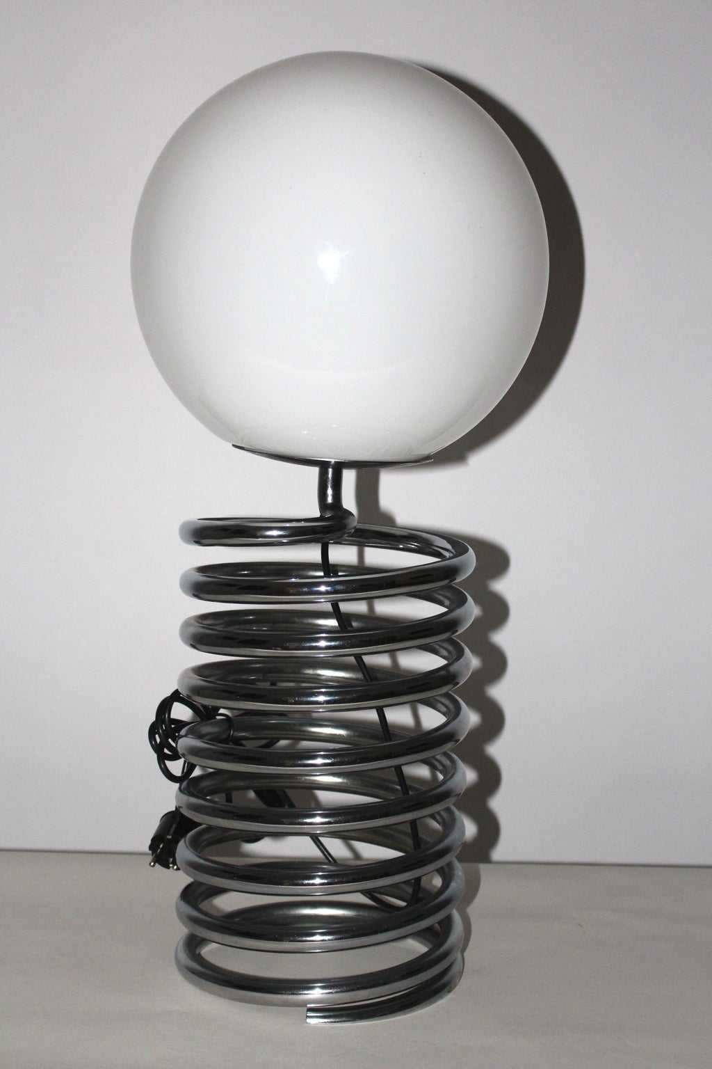 This table lamp shows a chromed spring base with an opal shade. Also onesocket E 27 and on/off switch. This early version is very rare and documented. Good Vintage Condition All measures are approximate.