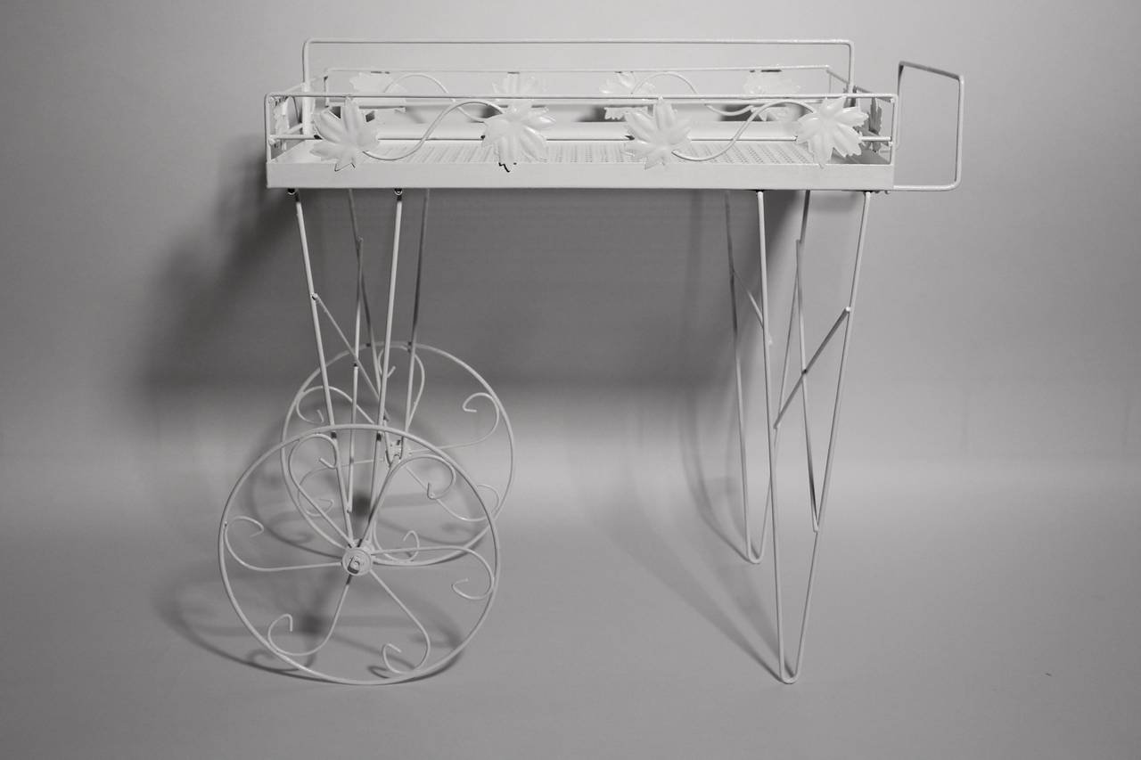 Lovely Italian bar cart or serving table, which is  decorated with wine leaves and equipped with two wheels. Made of perforated sheet metal and wire steel.  Newly white lacquered and in very good condition. All measures are approximate.