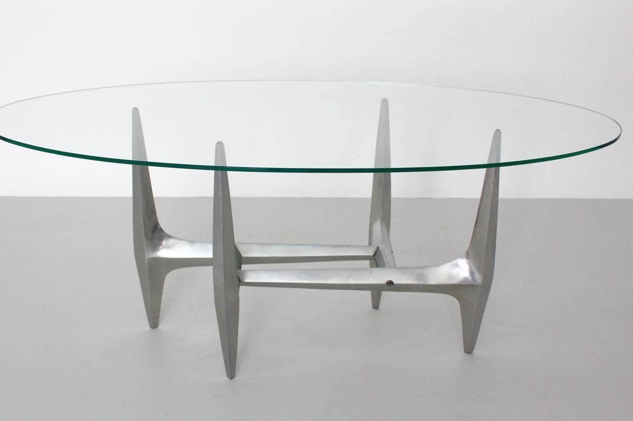 A bizarre structural high-quality mid century modern vintage coffee table by Knut Hesterberg, which was made out of a polished aluminium base and an oval clear glass top. Produced by Ronald Schmitt, Germany in the 1960s. Very good vintage