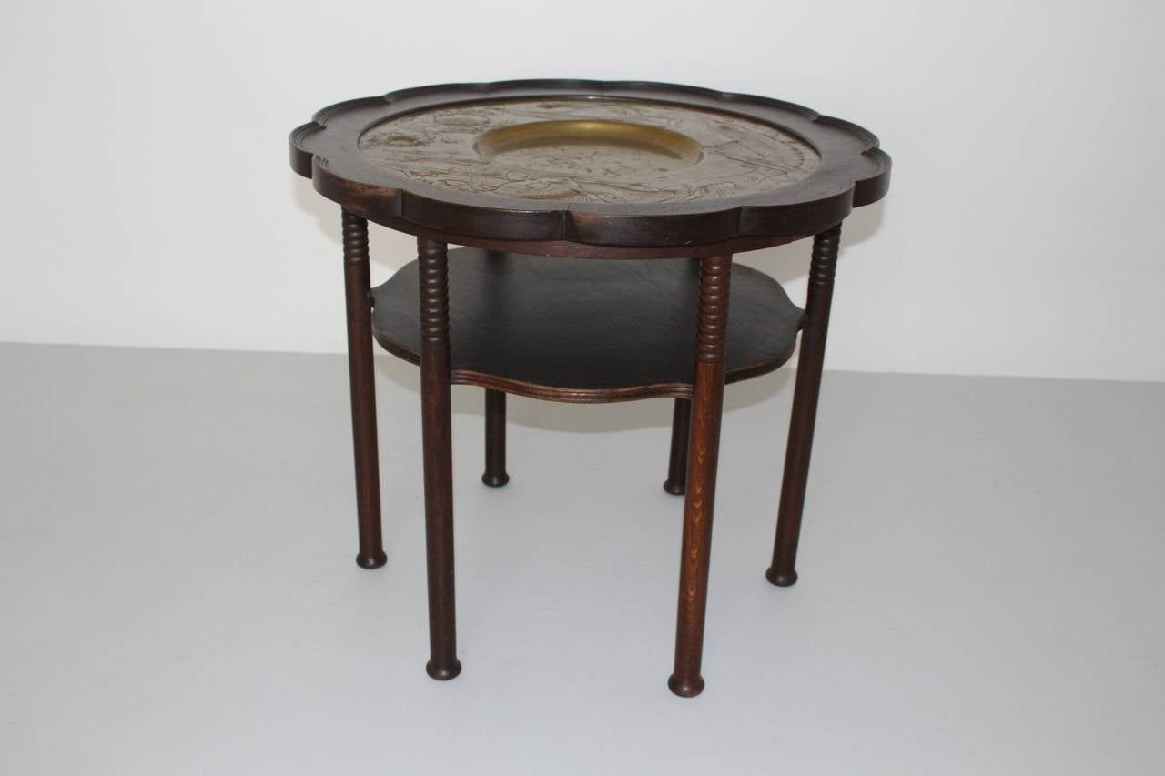 A Jugendstil vintage coffee table style Adolf Loos, which shows two tiers with a copper and brass drifted tabletop. While the beautiful metal tabletop shows fishes, crabs with brass patina, the framing has an elegant slightly curved shape.